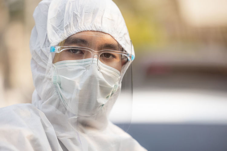 Medical scientist in ppe uniform wearing a face mask protective person
