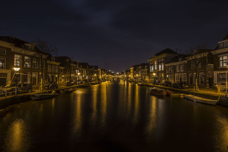 Boats Moored In Illuminated City Against Sky At Night