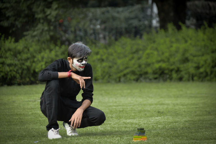 Full length of teenager boy with face paint crouching on grass at park