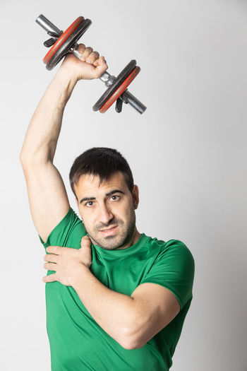 Portrait of young man holding camera over white background