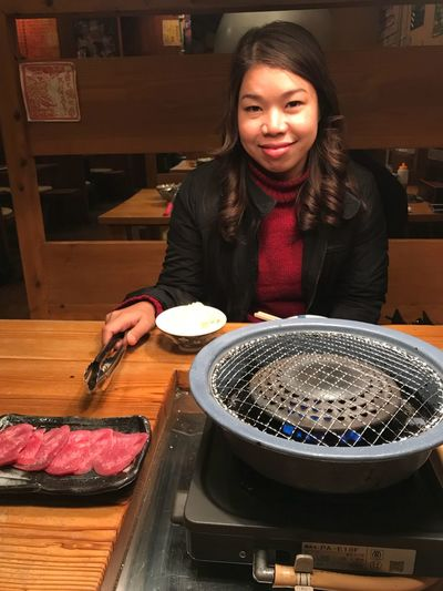 Portrait Of Smiling Woman With Barbecue Grill On Table At Restaurant