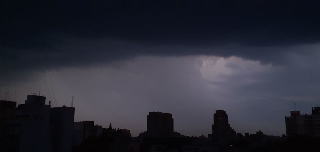 Silhouette buildings in city against storm clouds
