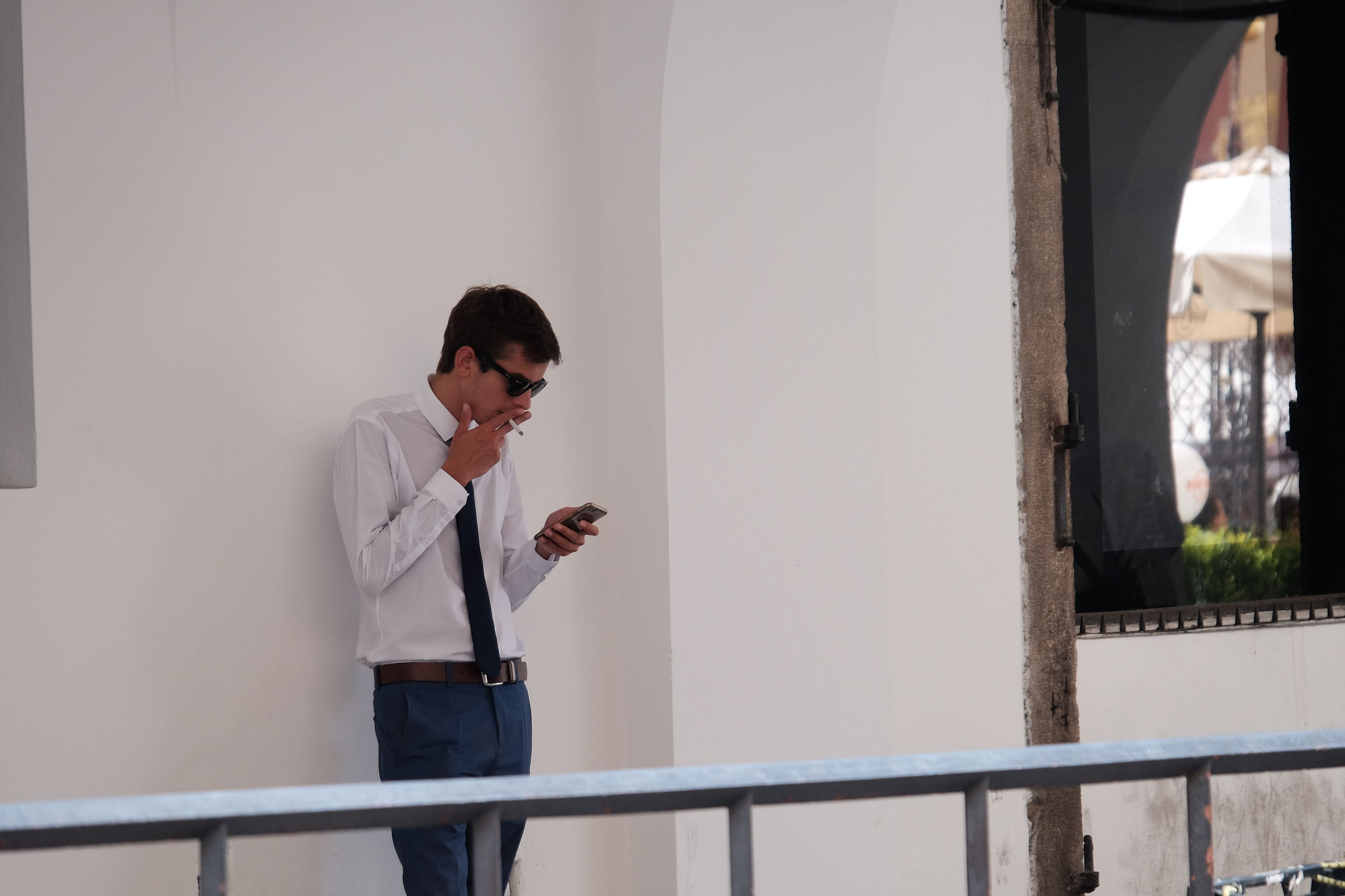YOUNG MAN USING MOBILE PHONE WHILE STANDING ON LAPTOP