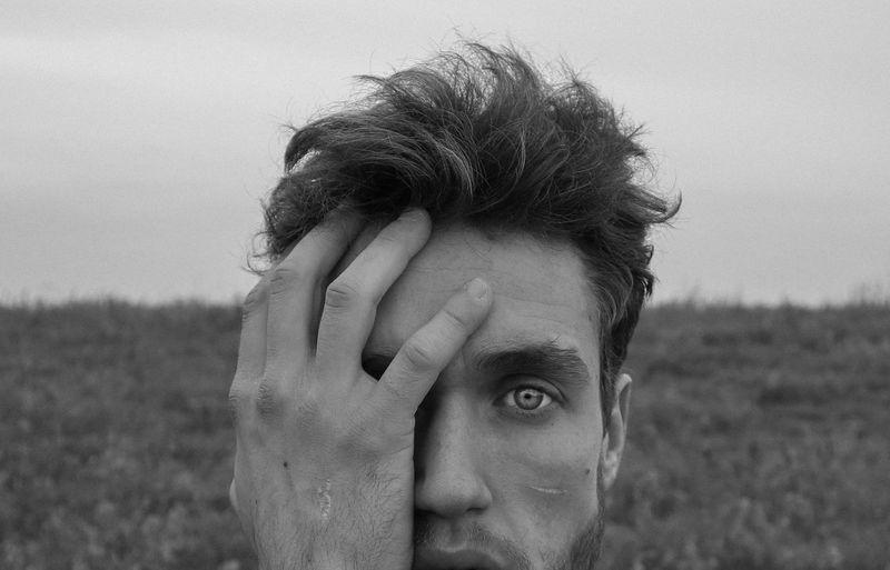 Close-up portrait of man against sky