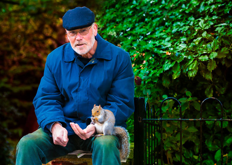 A lonely man makes friend with a squirrel Alone Animal Animal Themes Animals In The Wild Close Up Colchester Composition Day Focus On Foreground Friendship Front View Innocence One Animal Park Perspective Portrait Sitting Squirrel Togetherness Wildlife