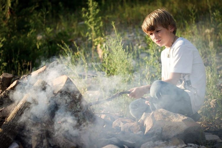 Boy looking at bonfire emitting smoke at campsite