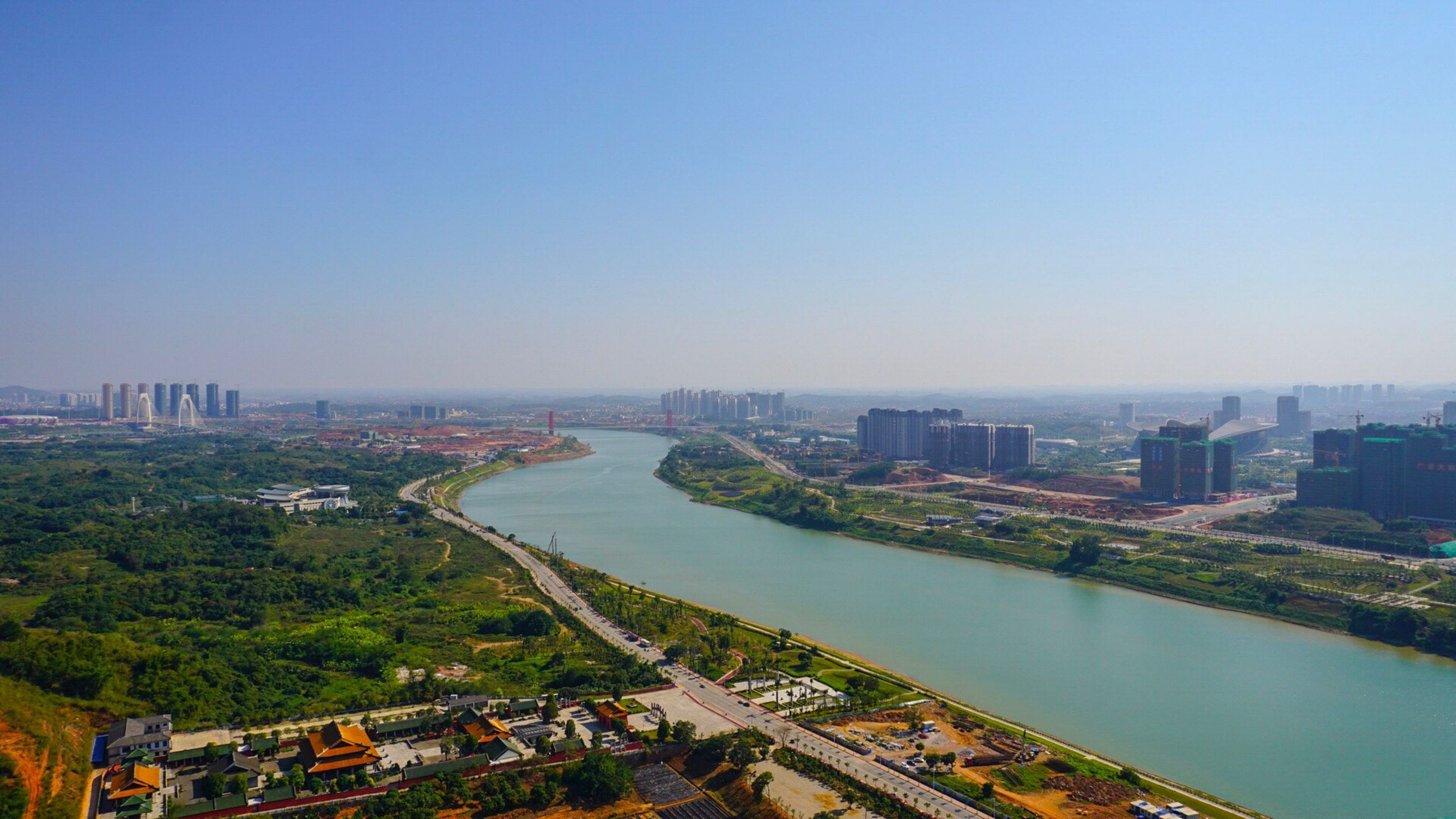 city, cityscape, architecture, high angle view, building exterior, transportation, clear sky, river, travel destinations, built structure, skyscraper, travel, outdoors, modern, urban skyline, city life, aerial view, bridge - man made structure, waterfront, no people, water, growth, nautical vessel, connection, illuminated, tree, sky, day