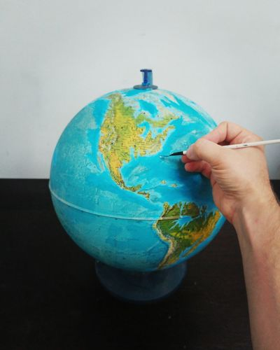 Cropped hand of man marking on globe at table