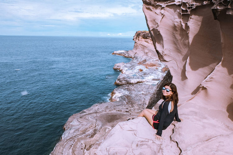 Woman wearing sunglasses sitting on rock formation by sea