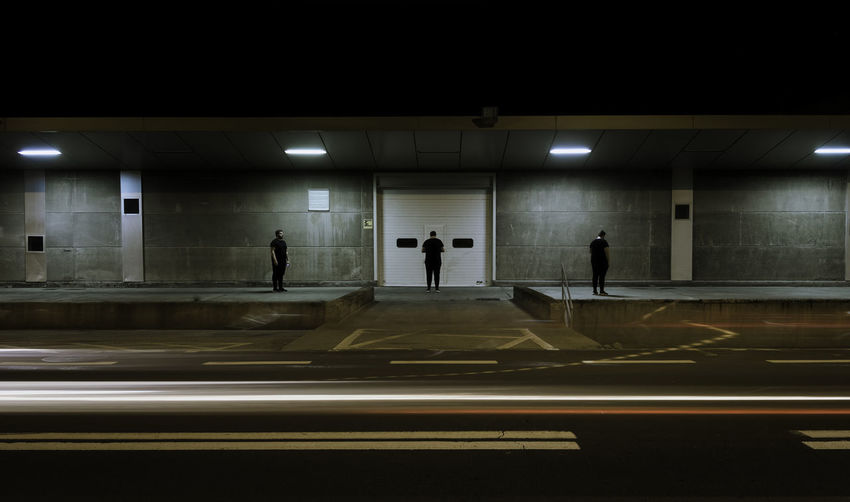Multiple image of man standing by illuminated building at night