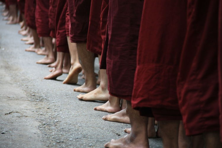Low section of monks standing on road