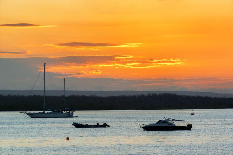 Boats sailing in sea at sunset