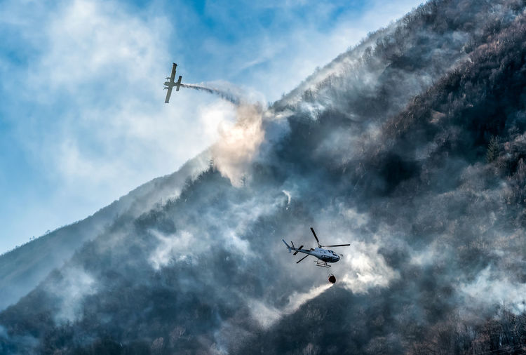Aerial view of airplane and helicopter extinguishing fire in forest