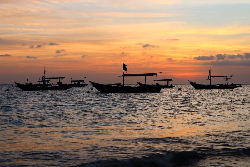 Silhouette boats in sea against sky during sunset