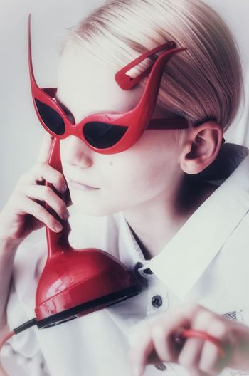 Close-up of retro style girl wearing sunglasses while holding phone against gray background