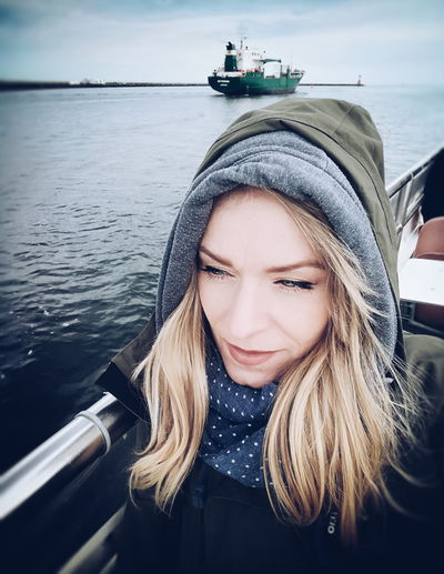 Close-up of smiling woman wearing warm clothes in boat