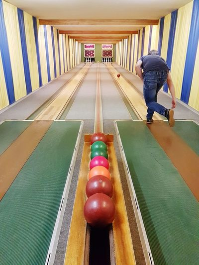 Two People Ball Arcade Full Length Lifestyles Playing Casual Clothing Males  Child People Boys Sport Childhood Men Leisure Activity Real People Indoors  Place Of Worship Built Structure Architecture Multi Colored Bowling Alley Bowling Kegeln Indoors  Males