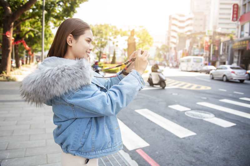 Side View Of Woman Photographing While Standing On Sidewalk In City