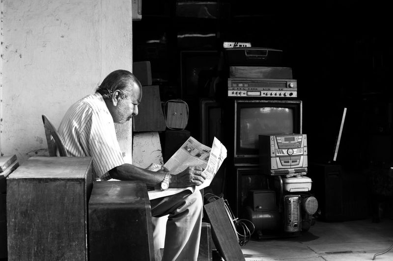 Man reading newspaper while sitting outside shop