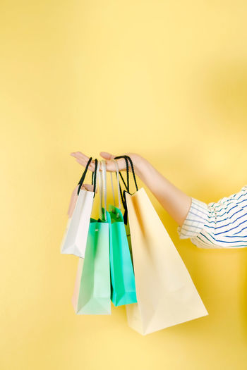Cropped hand holding shopping bags against yellow background