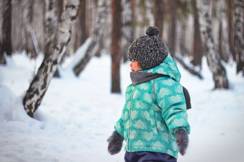Girl in warm cloth walking on snow covered landscape
