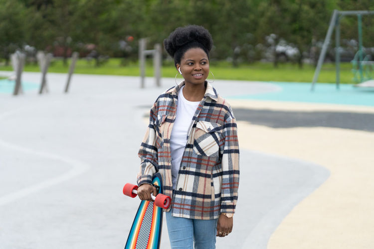 Smiling young woman holding skateboard while standing outdoors