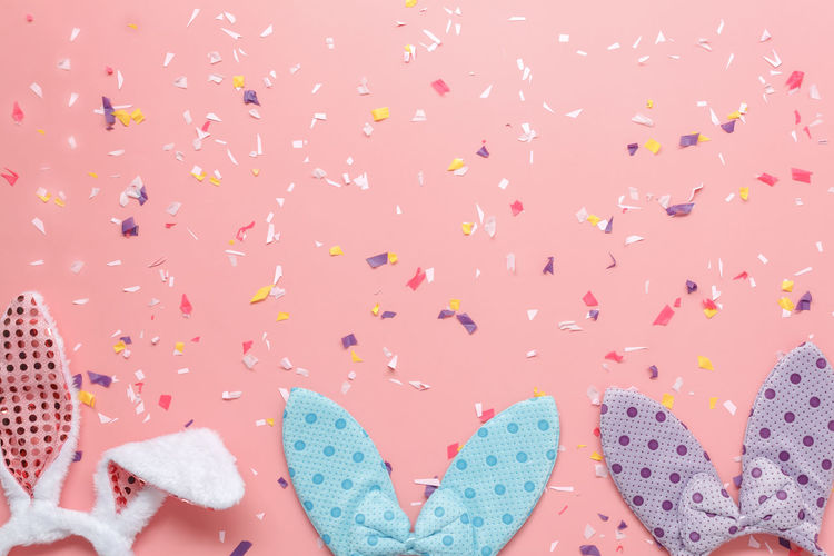 Directly above shot of bunny headband with confetti over colored background