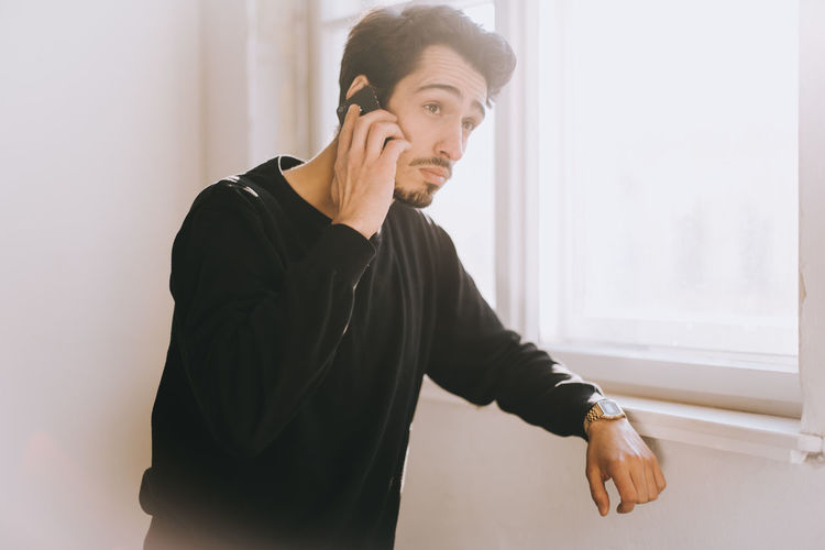 young latino man on the phone Light Man Sunlight Waiting Arab Cheerful Handsome Indoors  Latino Lensflare Lifestyles One Person Phone Talk Photo Photography Real Life Real People Sceptical Selfie Serious Standing Using Phone Window Window Light Wireless Technology