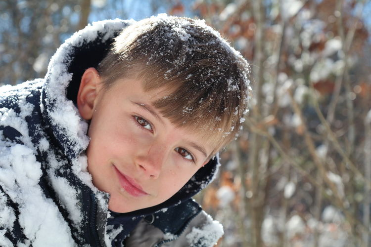 Close-up portrait of smiling boy in snow