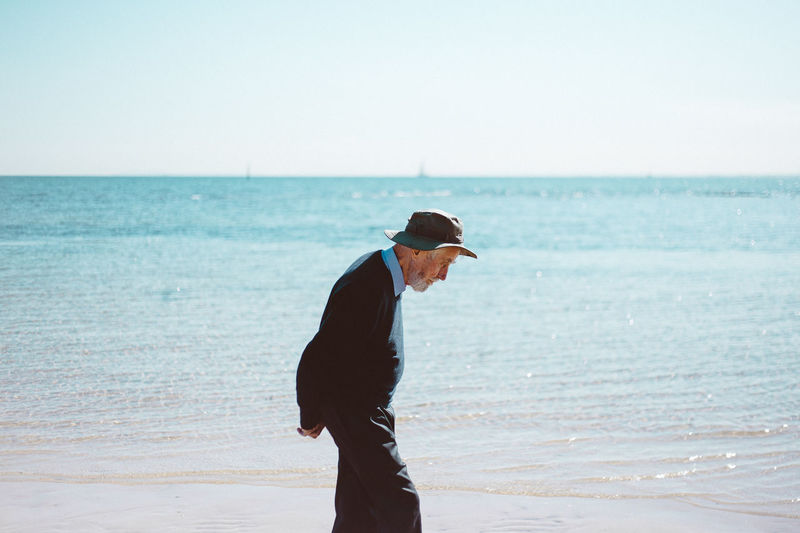 Full length of man standing on beach against sky