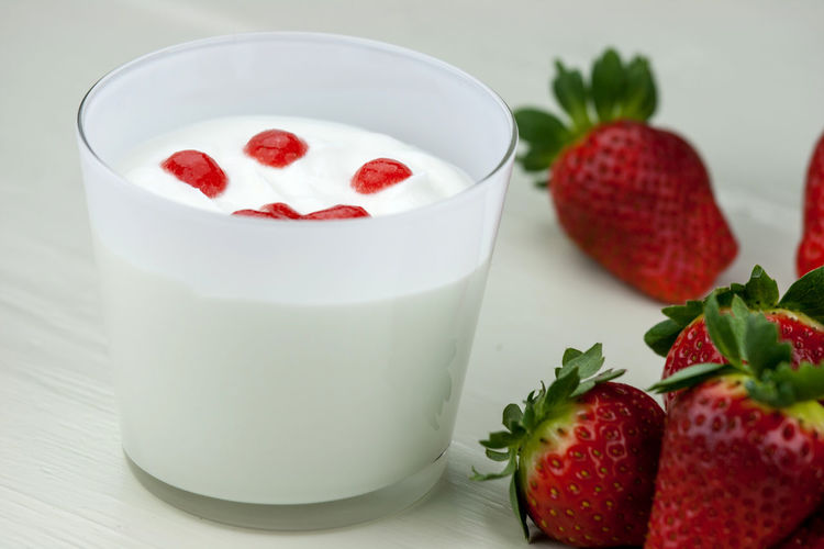 Close-up of strawberries by yogurt against white background
