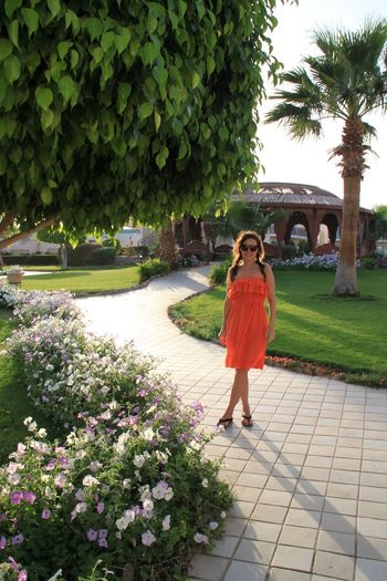 Full length of young woman in orange dress standing at park