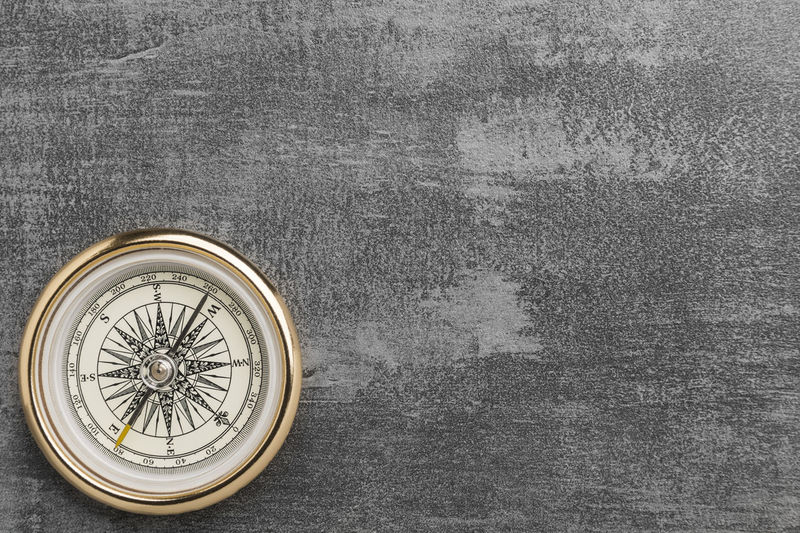 Golden navigational compass on a vintage gray background Gray Compass Vintage Cement Concrete Close Up Adventure Guidance Decisions Travel Purpose Philosophy Dilemma Planning Strategy Direction Grunge Leader Table Goal Directly Above Round Concept Nautical Navigation