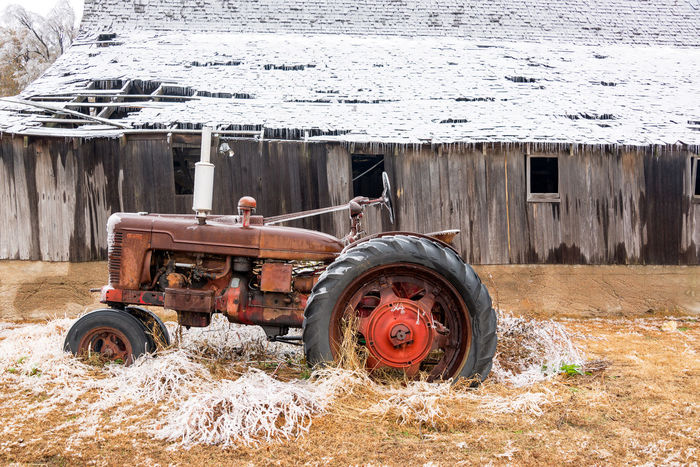 Old antique tractor covered in ice with a snow covered barn near Burrton, Kansas Country Farm Grass Ice Storm Weather Winter Agriculture Architecture Browm Building Exterior Countryside Fence Icy Land Vehicle Leaf Leaves Outdoors Plains Season  Seasons Snow Snowfall Snowy Transportation