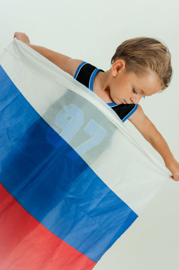 Tilt Image Of Boy Holding Flag While Standing Against White Background