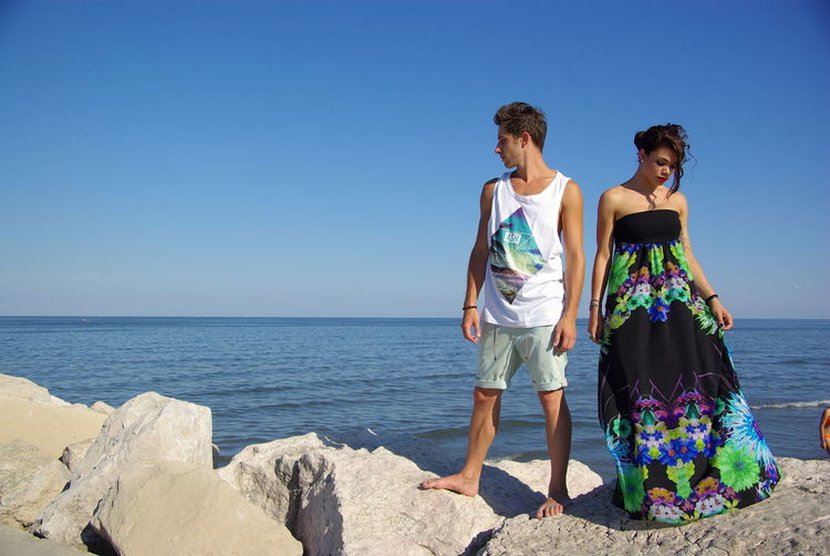 Full Length Of Man And Woman Standing On Rock Against Sea