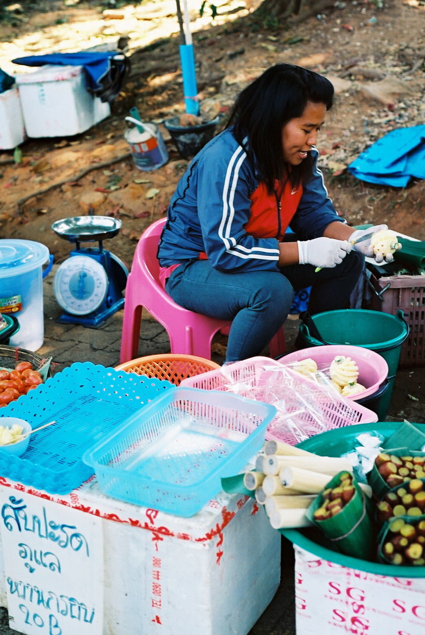 real people, day, market vendor, market stall, small business, retail, market, one person, outdoors, container, choice, food and drink, can, sitting, holding, women, food, full length, one woman only, freshness, adult, adults only, young adult, people