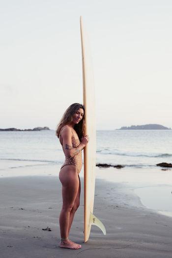 Young woman in bikini on beach against sky