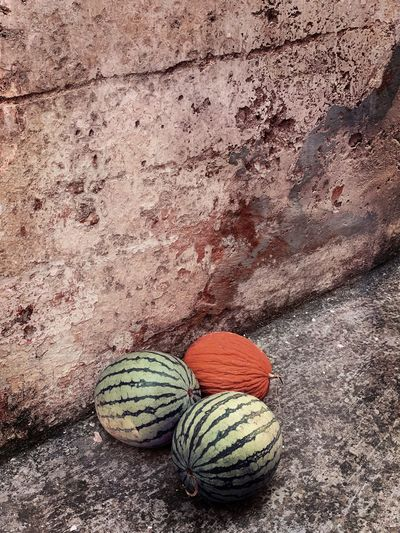 High angle view of balls on rock against wall