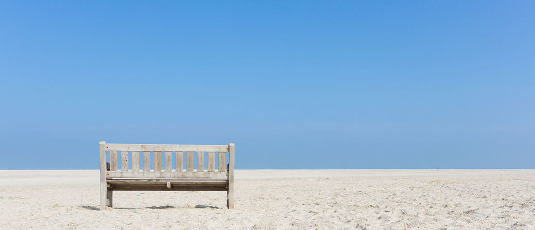 Wooden bench at empty beach Bench Beach Blue Clear Sky North Sea Sand Sky Tranquil Scene Walchensee Zeeland