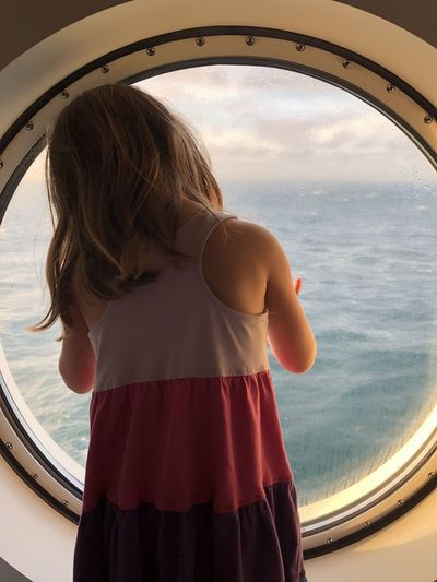 Rear view of woman looking out a circular window at sea against sky