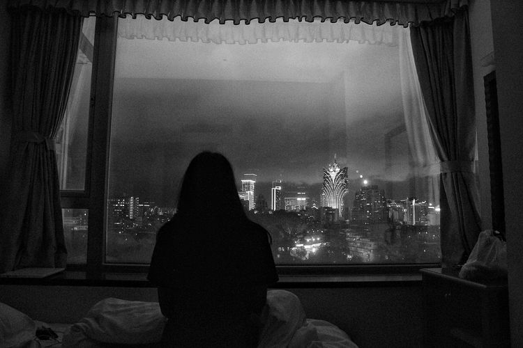 Rear view of silhouette woman looking at city through window at home