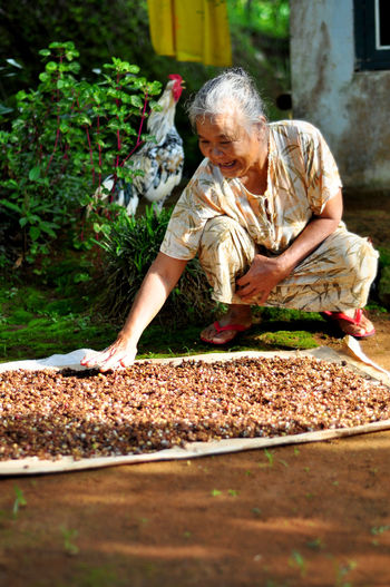 Full Length Of Senior Woman Drying Cloves While Crouching By Plants At Yard