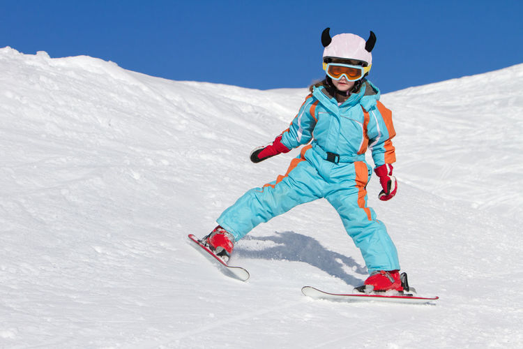 Teenage girl skiing skiing on snowy mountain