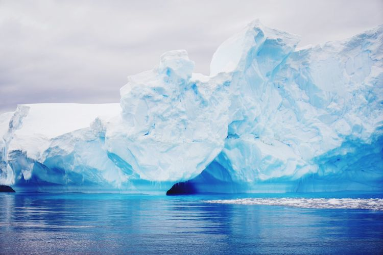 Scenic view of iceberg in sea against cloudy sky