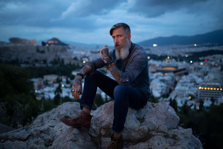 Attractive bearded man is sitting on the rock in the middle of Athens, smoking a cigarette One Person Architecture Building Exterior Leisure Activity Rock - Object Lifestyles Nature Front View City Full Length Casual Clothing Mid Adult Outdoors Cityscape Evening Landscape Athens Greece Acropolis Biker Hipster - Person Model Modern Beard Tattoo