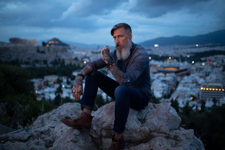 Portrait Of Mature Man Sitting On Rock Against Cityscape At Dusk
