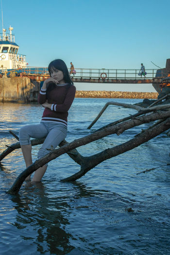 Portrait of teenage girl sitting on branch in river against clear sky