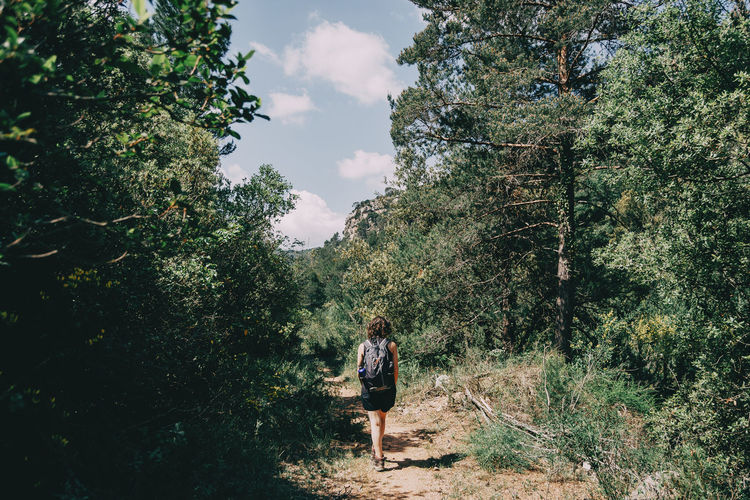 Girl walking along a small path in the mountain of prades, tarragona, spain. on a sunny summer day