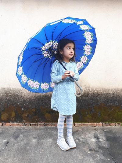 Thoughtful girl holding blue umbrella while standing against wall
